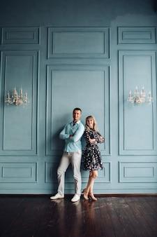 シャンデリアでクラシックな装飾が施された壁のそばに立っているエレガントなカップル