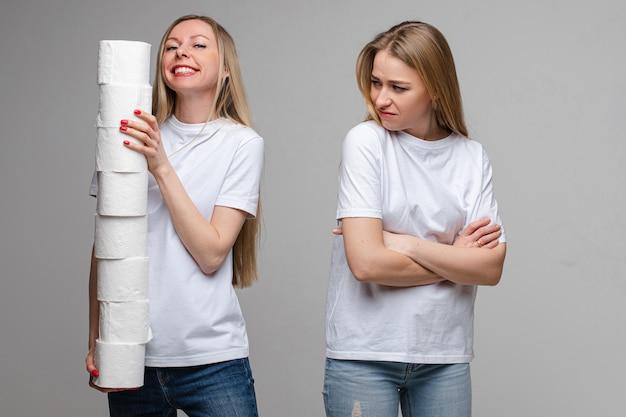 彼女の妹の横にあるトイレットペーパーのロールでポーズ笑顔の女性