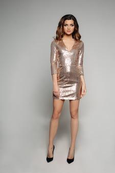 Красивая модель с длинными волнистыми волосами в хвосте в мерцающем черном платье и на каблуках