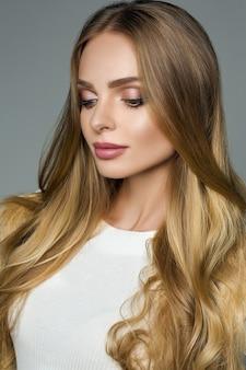 太いブロンドの髪と灰色の上の白いブラウスを持つ完璧な女性。