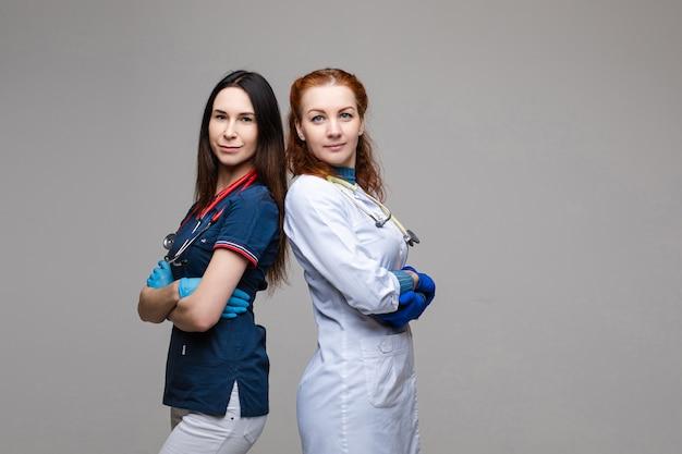 Портрет двух женщин-врачей в медицинской одежде с фонендоскопом вокруг их шеи, фотография, изолированная на белом пространстве