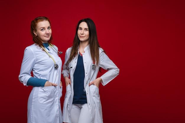 Портрет двух женщин-врачей в медицинской одежде с фонендоскопом вокруг их шеи, фотография изолирована на красной стене