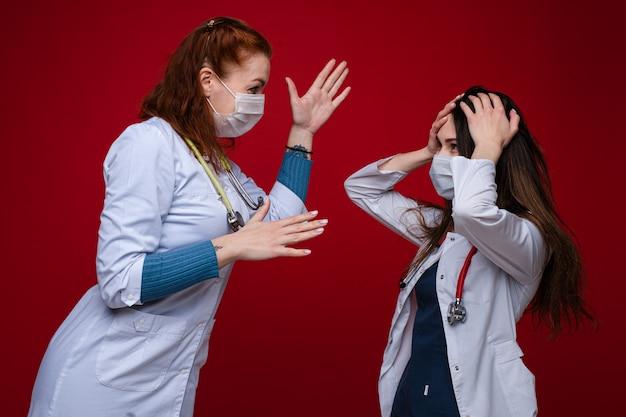 Спорят две женщины-доктора в медицинской одежде со стетоскопом на шее