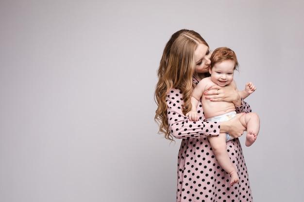 Молодая мать держит ребенка на руках и смеется