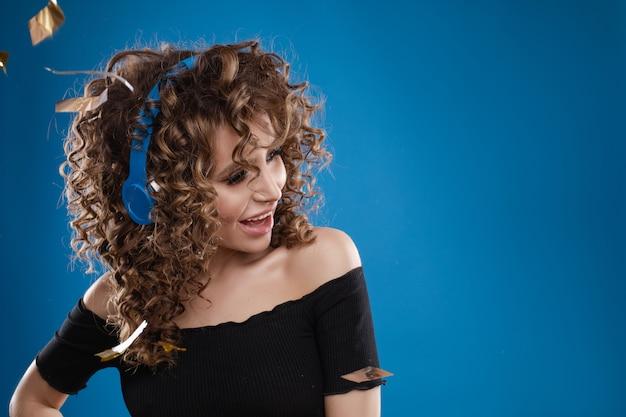 Женщина в наушниках слушает музыку и танцы