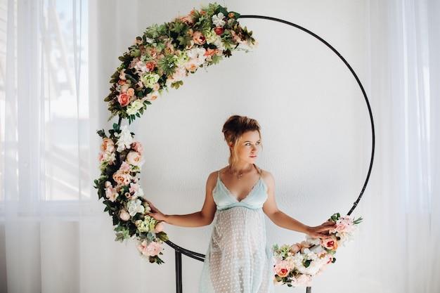 花が付いている装飾の中ポーズネグリジェドレスで美しい妊娠中の女性。
