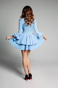 Неузнаваемая женщина с волнистыми волосами держит юбку своего платья.