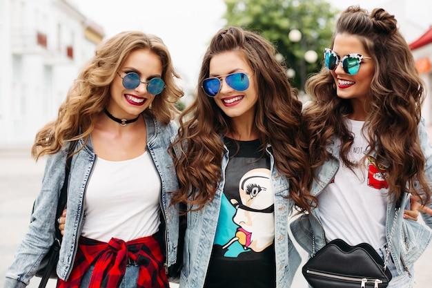 サングラスと流行の服を着たファッショナブルな女性が通りでカメラに笑顔します。