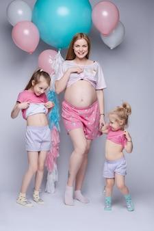 Смешное фото великолепной беременной матери с двумя дочерьми, глядя на их животы.