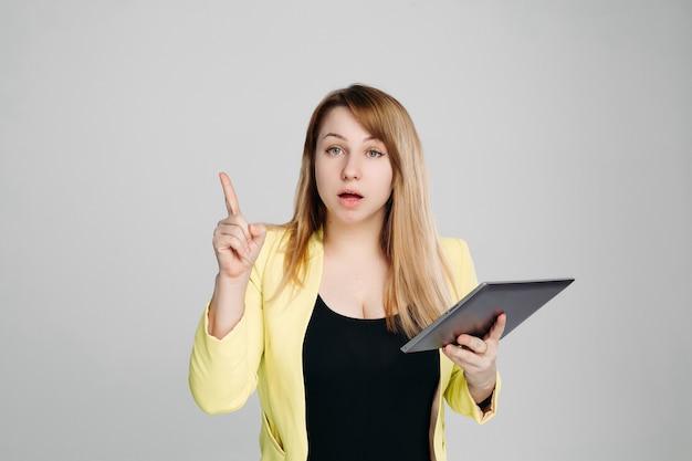 タブレットコンピューターを押しながら指を上向きにする女性の肖像画