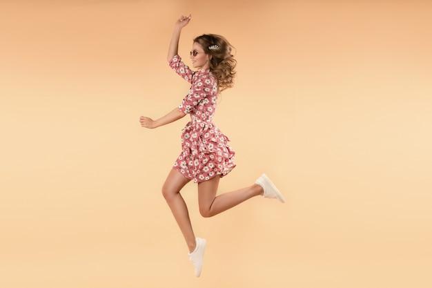 Женщина в розовом цветочном платье прыгает и смеется