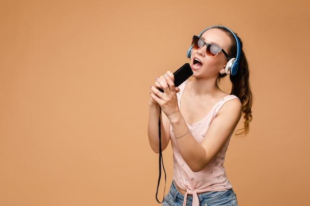 Женщина в наушниках слушает музыку и поет