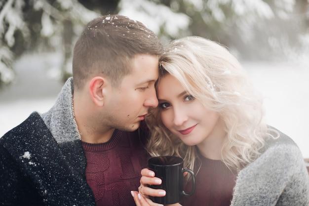 カップルのボーイフレンドとガールフレンドのコーヒーカップを保持しています。
