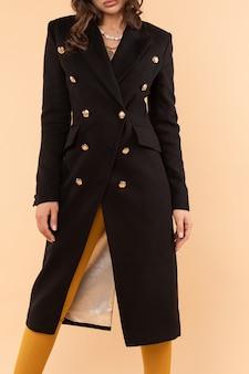 Потрясающая модная женщина в пальто, как платье и высокие каблуки