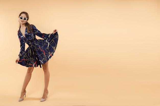 Элегантная брюнетка женщина в платье и каблуки и солнцезащитные очки.
