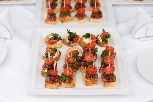 Вкусные тосты подаются на белых тарелках на свадьбе