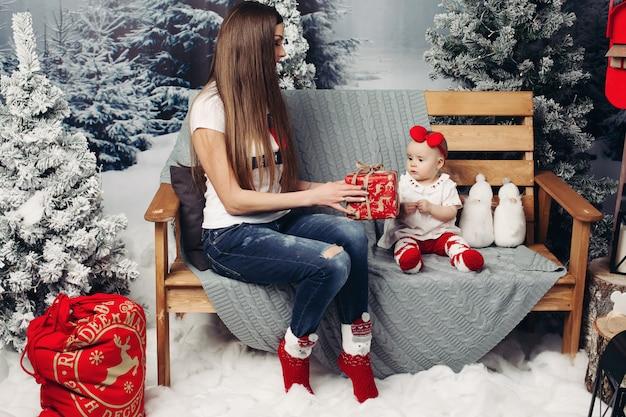 愛情深い母親が赤ちゃんとクリスマスツリーを飾る