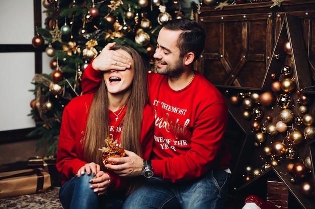 クリスマスに彼のガールフレンドの目を覆っている幸せな男