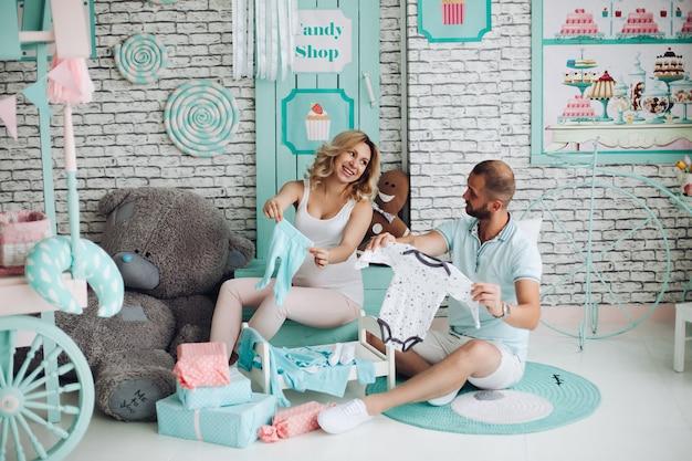 妊娠中の女性と彼女の素敵な表示赤ちゃん服お互い