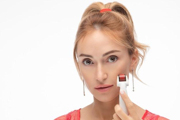 マイクロニードルメソセラピーローラーを持つ女性。白で隔離します。