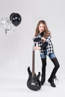 かわいい赤ちゃんの女の子ロックスターのエレクトリックギターを演奏し、風船に囲まれた歌を歌う