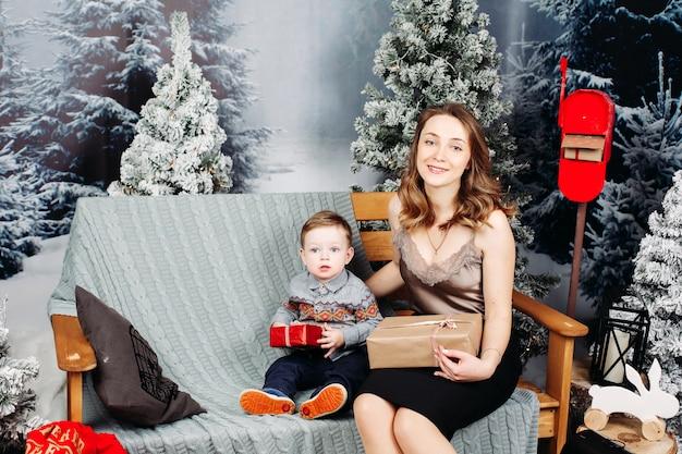幼い息子の木にクリスマスの装飾を示す幸せな親。