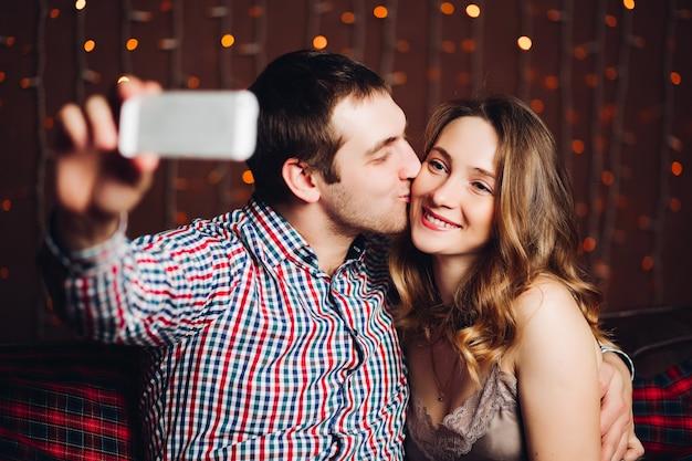 Счастливые и положительные пары делая автопортрет в украшенной для студии рождества.
