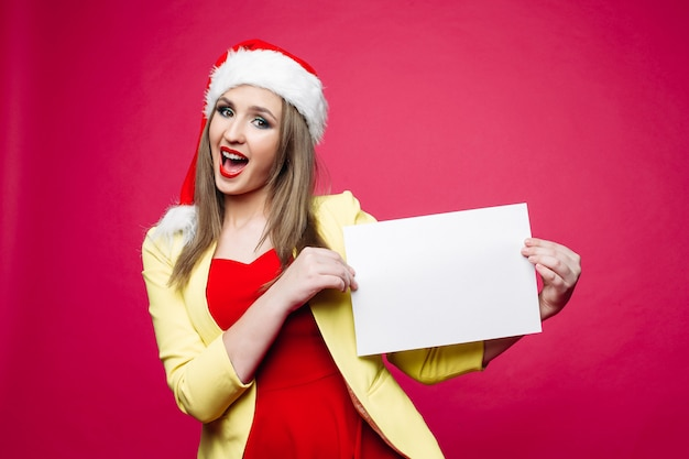 サンタ帽子で紙の笑顔の女の子空白のシート。