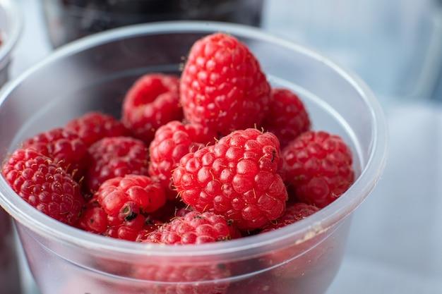 Сладкая, вкусная, красная и свежая малина в маленьком пластиковом стаканчике