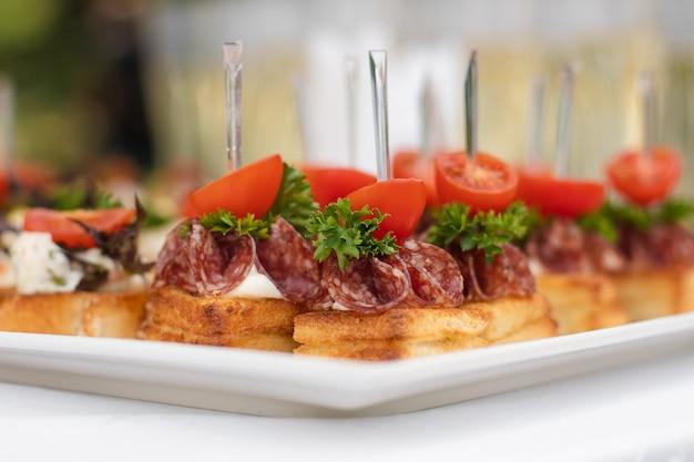 スナックカナッペ揚げパントマトパセリとサラミを提供するクローズアップの大皿