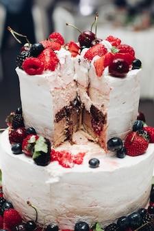 ベリーと美しいウェディングケーキ。クローズアップでウエディングケーキをスライスしました。