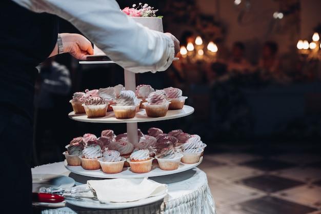 ケーキとカップケーキを提供するウェイターの後ろからの眺め