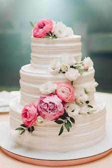 ホワイトクリームのアイシングで覆われた食欲をそそる新鮮なペストリーケーキとテーブルの上に役立つ甘い花を飾る