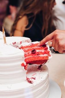 赤いベルベットのケーキのスライスを取る人。