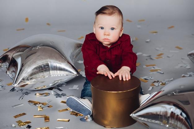 Мальчик с золотой подарочной коробке на полу с конфетти и воздушные шары.