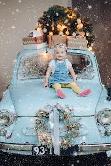 クリスマスに飾られた青いレトロな車に座っている甘くてファッショナブルなかわいい女の子の正面図。