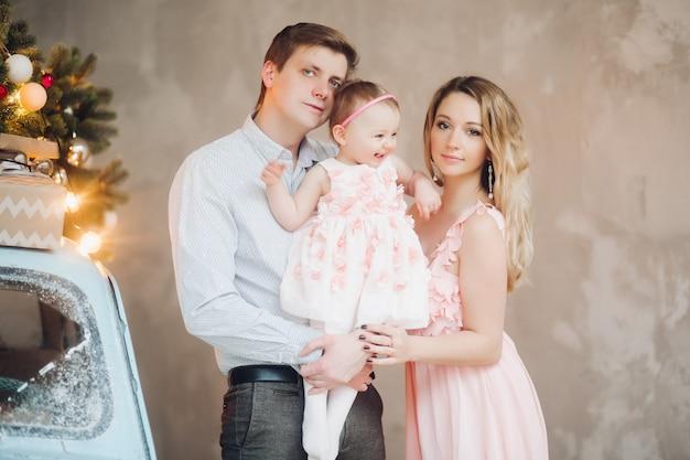 青いレトロなクリスマス車の近くで一緒にポーズ美しい家族。