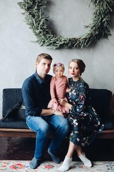 両親と娘が大きなモミの花輪の下でソファーに座っていた。