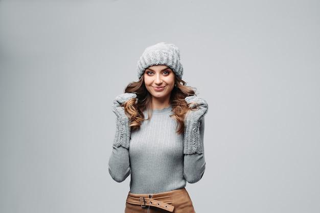 暖かい灰色の帽子とセーターで美しい笑顔の女の子。