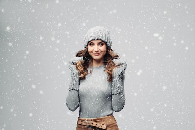 Красивая улыбающаяся девочка в теплой серой шляпе и свитере.