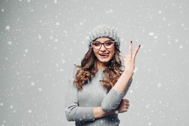 Красивая девушка в свитер, показывая мир и торчали.