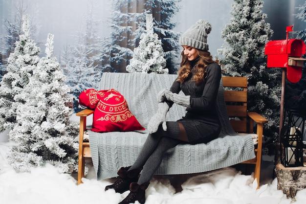 クリスマスツリーの中でベンチに座っている灰色の女性。