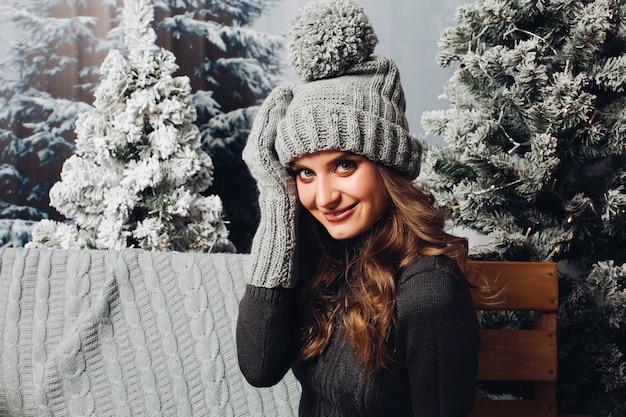 灰色のニット帽子と手袋で美しい女性。