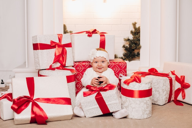 クリスマスツリーの下でポーズをとって白いドレスでかわいい子。