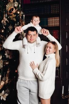 両親は赤ちゃんとポーズします。背後にあるクリスマスツリー。