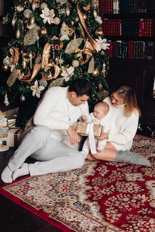 装飾されたリビングルームでポーズをとる家族。愛らしい女性、男と赤ちゃんが居心地の良い白いニットの服を着ています。