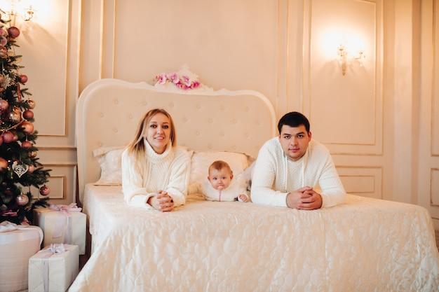 Родители лежат с ребенком на кровати