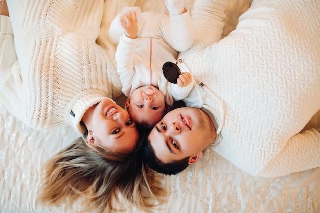 赤ちゃんと一緒にベッドに横たわっている親