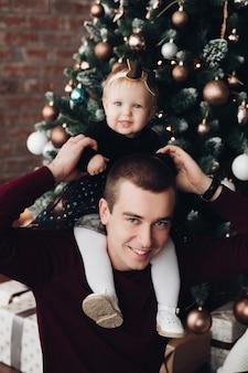 Милая маленькая девочка сидит на шее отца