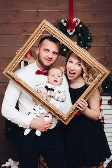 Семья элегантности стоящая около камина, обнимающая сына и целующаяся